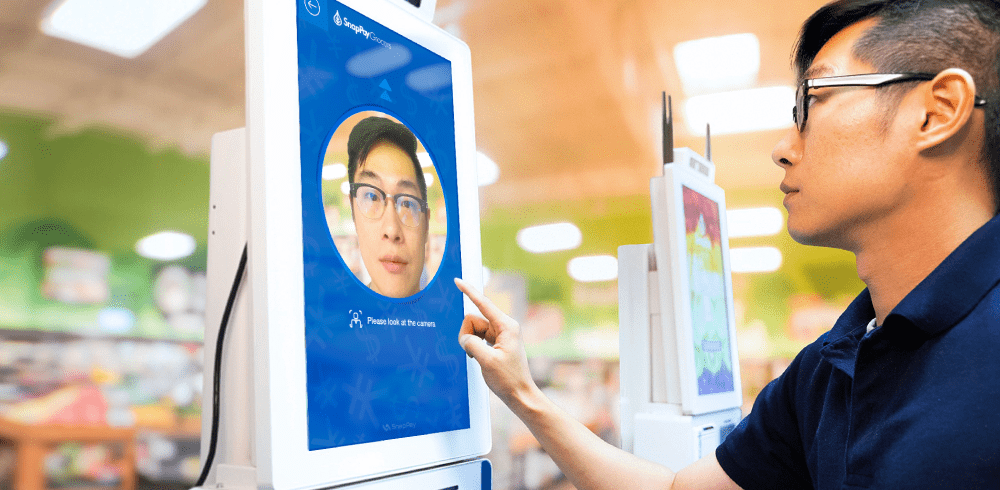 a young man touching a large screen with his face on it